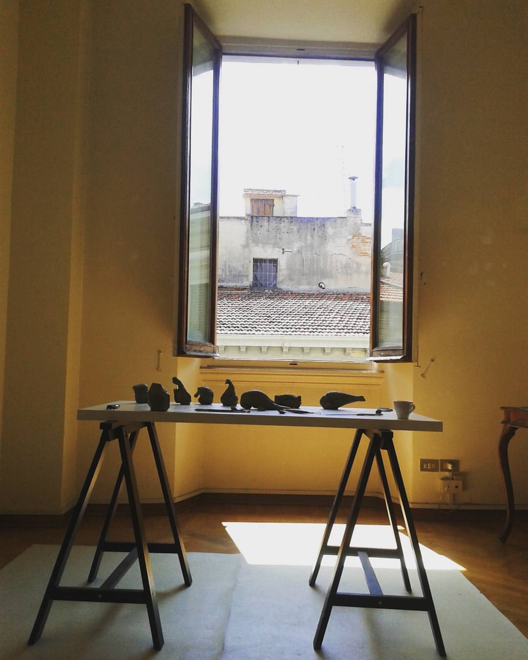 Series of small sculptures sitting on a workbench in a sunny room with an open window overlooking a rooftop