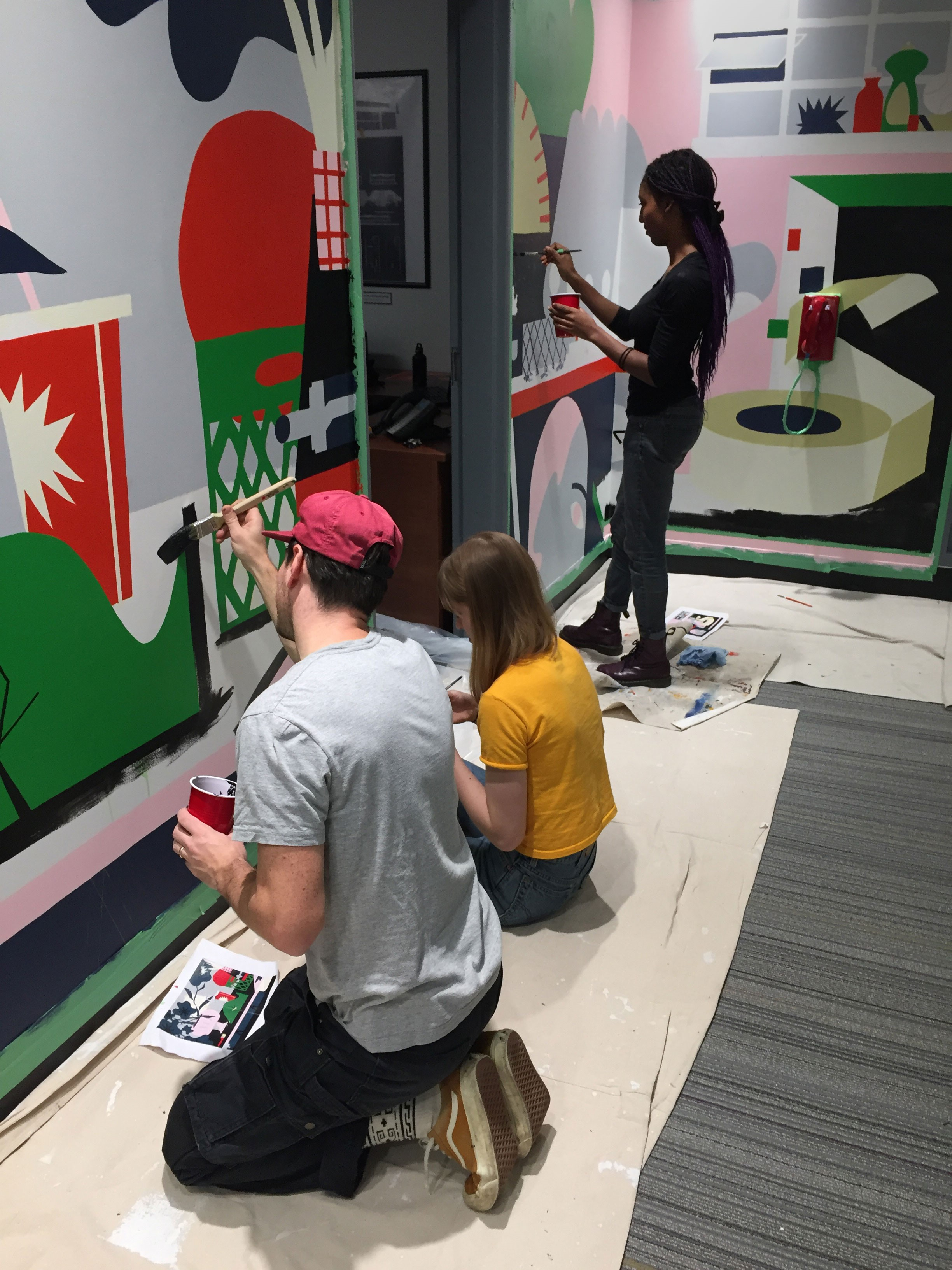 Three people painting the mural