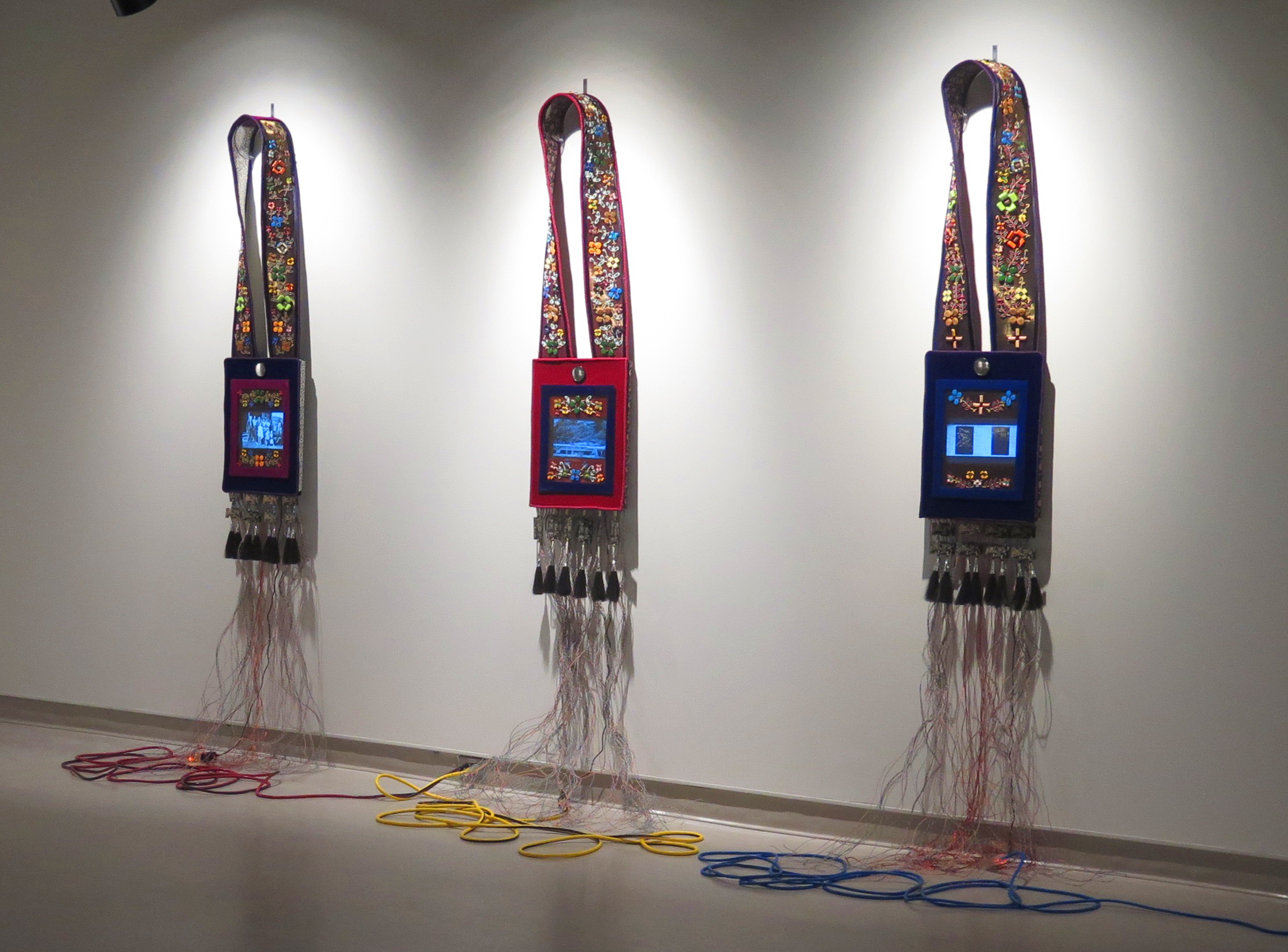 Three beaded cloth and screen installations hanging in a gallery wall
