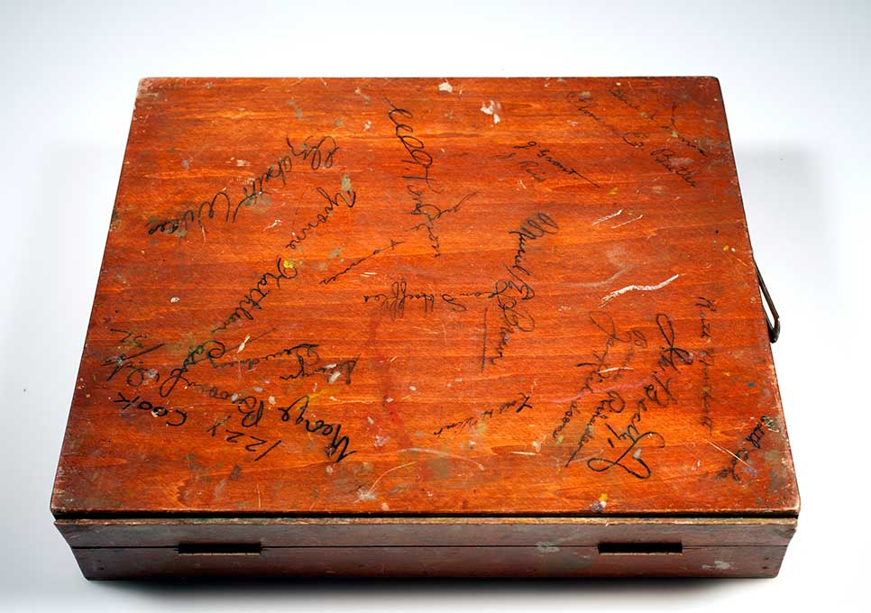 Image of a closed paint covered wooden box used to store tubes of paint with various signatures written on the lid.