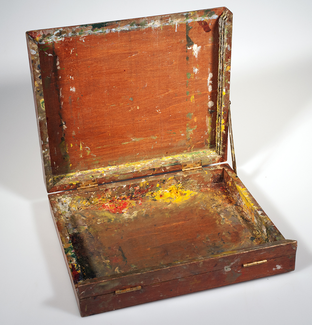 Image of an open paint covered wooden box used to store tubes of paint.