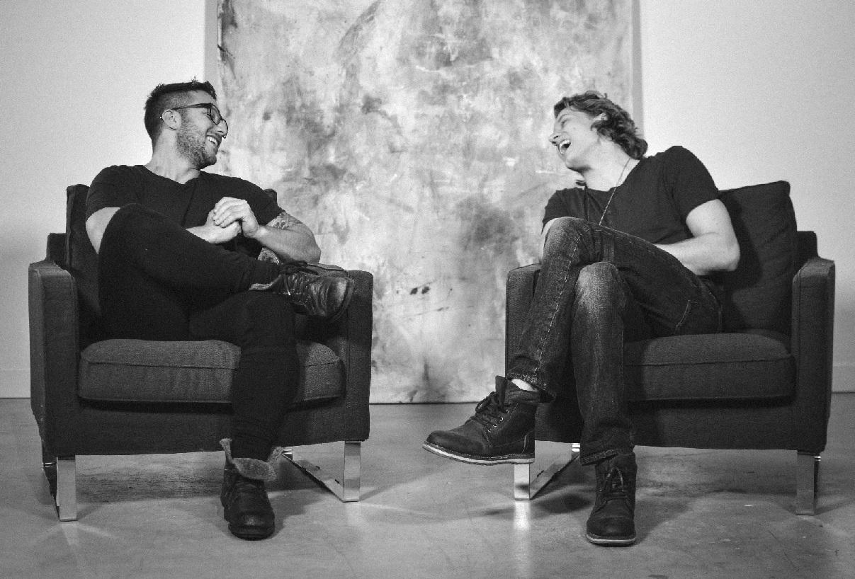 Photograph Elliott Muscatt and Chris Godfrey sitting on black chairs.