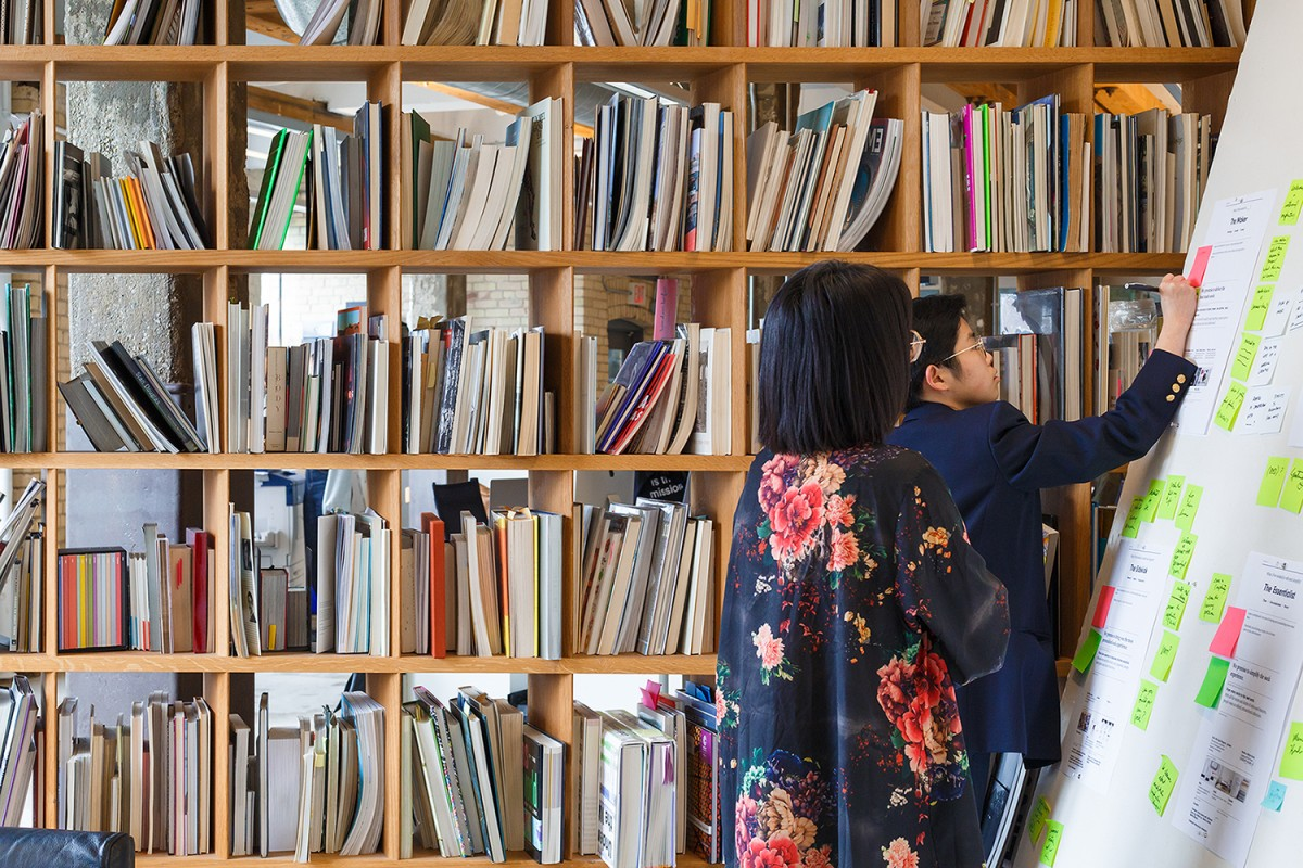 Image of two people working on board on right with bookshelf wall in back