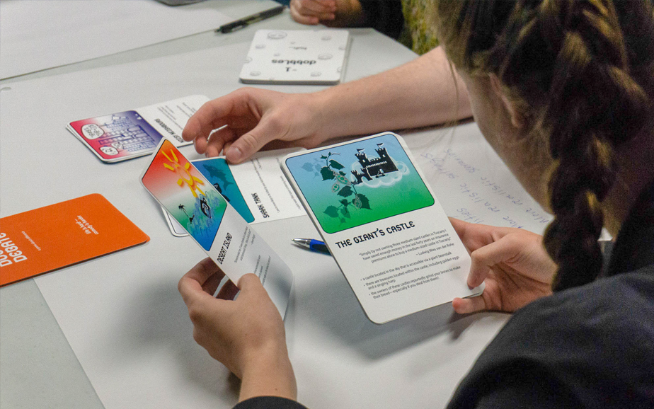 Photograph of a participant handling two Dobble Debate cards in play