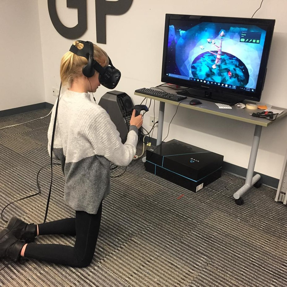 Photograph of girl kneeling while playing a VR game
