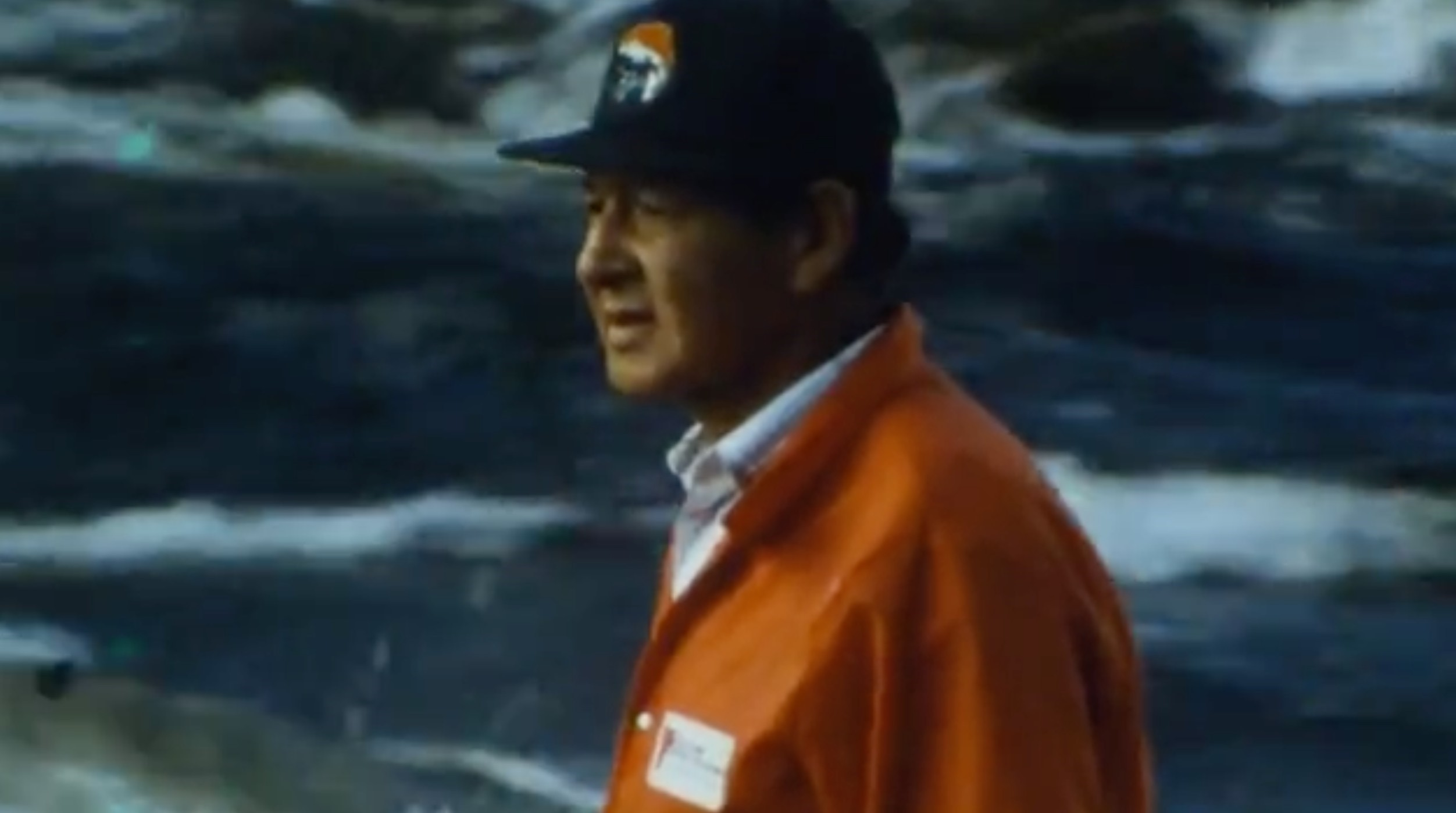 "video still from ""Lac La Croix (1998)"" of Ron Geyshick standing before a cloudy sky"