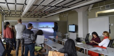 Photograph of Marcus Gordon presenting research on a large screen to a group of seated listeners in the visual analytic lab.