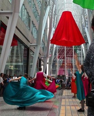 People dancing with long, brightly coloured dresses in large atrium.