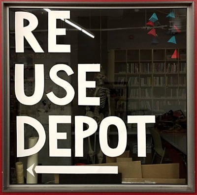 "Photo of office window with letters taped to it spelling out ""Re Use Depot"" with an arrow pointing left below the text"
