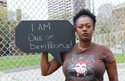 "Woman holding a sign that says ""I AM ONE OF DEM PEOPLE"""