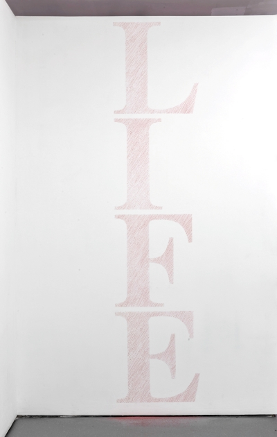 Block letters spelling LIFE vertically on a white wall