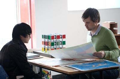 A teacher and student review a portfolio of work together at a table