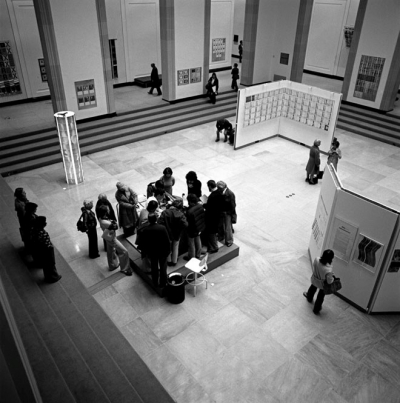 Black and white image of a group of visitors to the 1976 exhibition in Walker Court