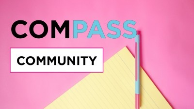 reads Compass Community on a pink background with yellow paper and blue pen