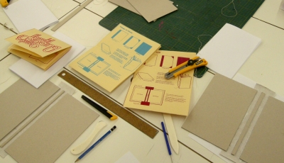 image of zine making materials including knives, rulers, pencils, paper and bone folders.