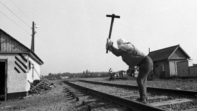 Photo of a person with a sledge hammer on railway
