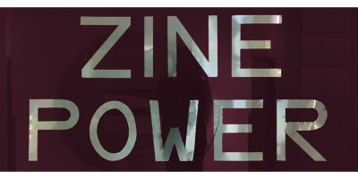 Photograph of Zine Power Exhibition sign. Metal letters on burgandy paper.