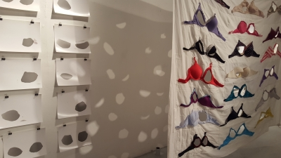 a number of bras sewn to a white sheet, some with cut outs