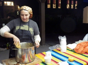 Photograph of Lisa Myers wearing an apron and stirring a pot