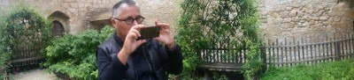 A photo of Pam Patterson in a garden pointing a camera phone