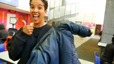 Student fixer with repaired jacket smiling and giving the thumbs up