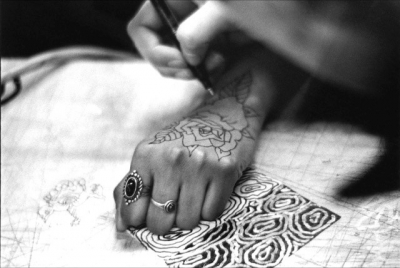 black and white photo of a womans hand being tattooed with Henna