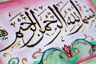 Close up image of Arabic letter forms in black and gold over decorative background