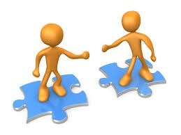 Clip art of two yellow figures shaking hands while standing on blue puzzles pieces