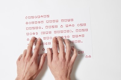 Two hands with finger tips running along red symbols printed onto a page.