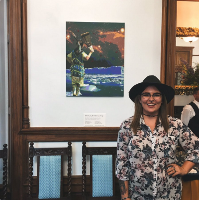 Chief Lady Bird standing with her artwork on display at Other Worlds
