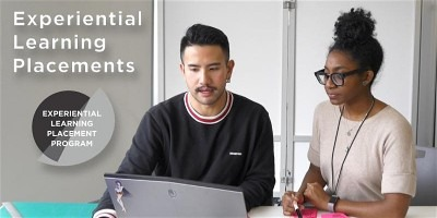 Two people talking over a laptop computer looking at screen. Exp two circle logo on left.