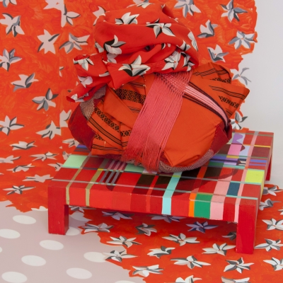 Graphic red/orange background, red wrapped package on red patterned table structure