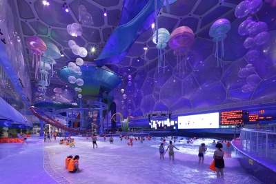 Children and families playing in an indoor waterpark lit with bright purple lights. Overhead jellyfish lights.