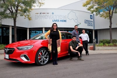 Four students standing in front of a red GM car
