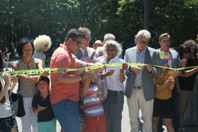 People lining up to cut a yellow ribbon