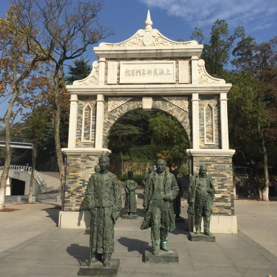 7 Statues underneath stone archway with Chinese sign