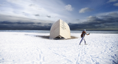 Image of a wooden structure on snowy beach with a man walking