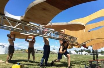 People hoisting up a sculptural installation