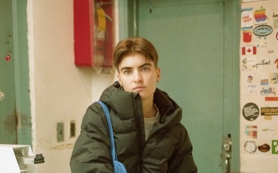 Photo of human with winter green coat sitting and staring at camera