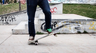 The legs of a person standing on a skateboard