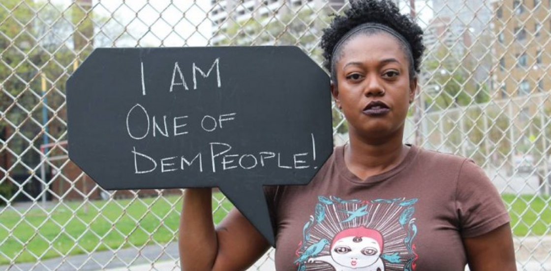 """Woman holding a sign that says """"I AM ONE OF DEM PEOPLE"""""""