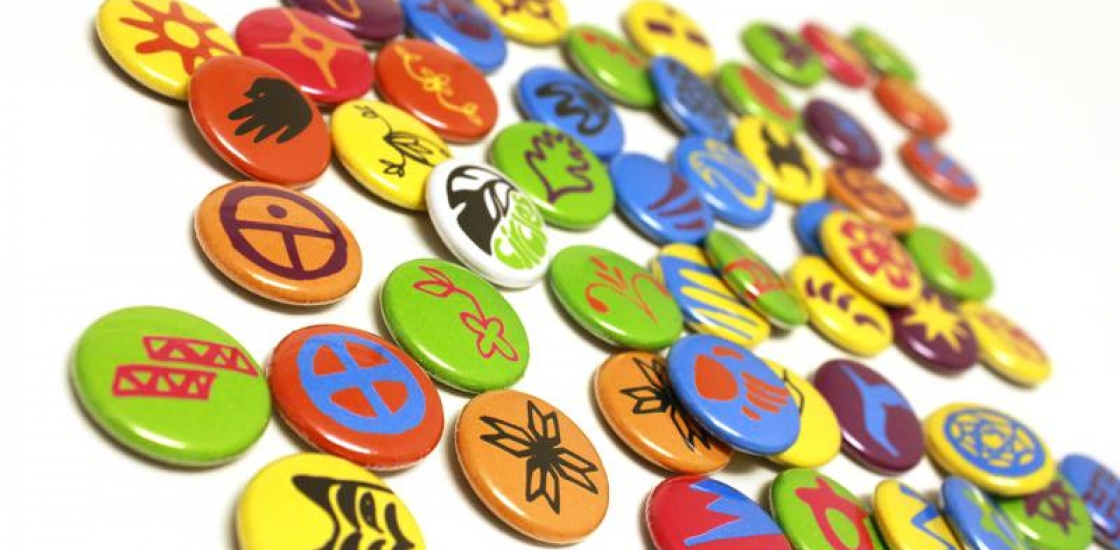 Multic-coloured button pins on a white background