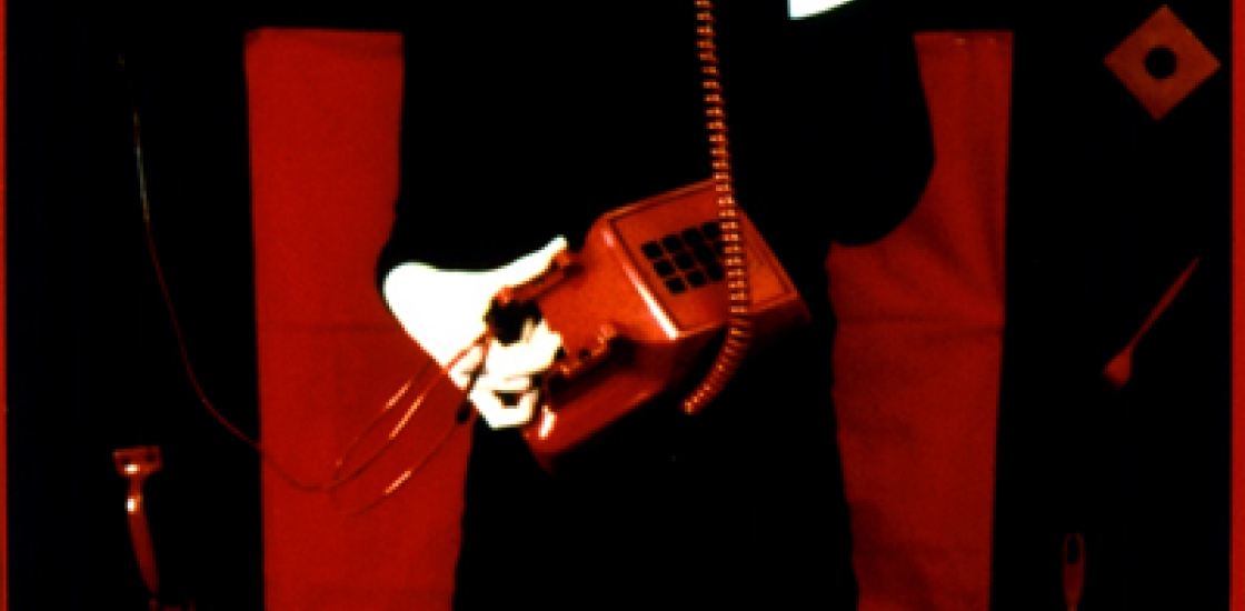 cropped photo of a woman in a black dress talking on a red telephone