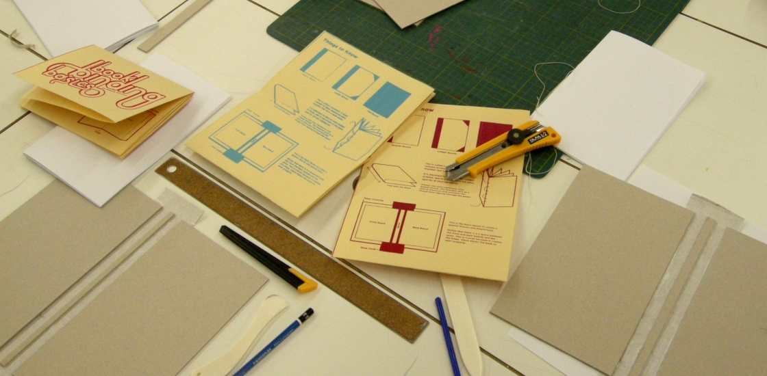 image of zine making materials such as paper, knives and bone folders