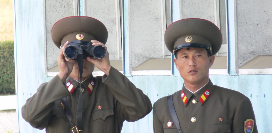 Image of two men in uniform one with binoculars