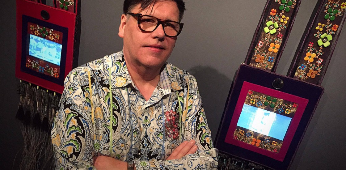 Photo of artist Barry Ace in front of his works
