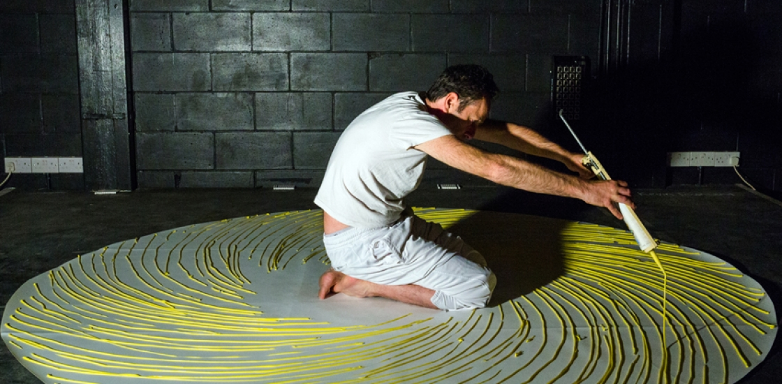 photo of a man on his knees painting yellow circles around himself