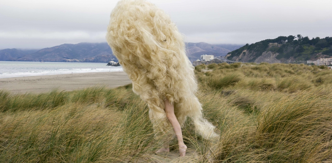 photo of fek=male figure with full body length of hair walking in the dunes