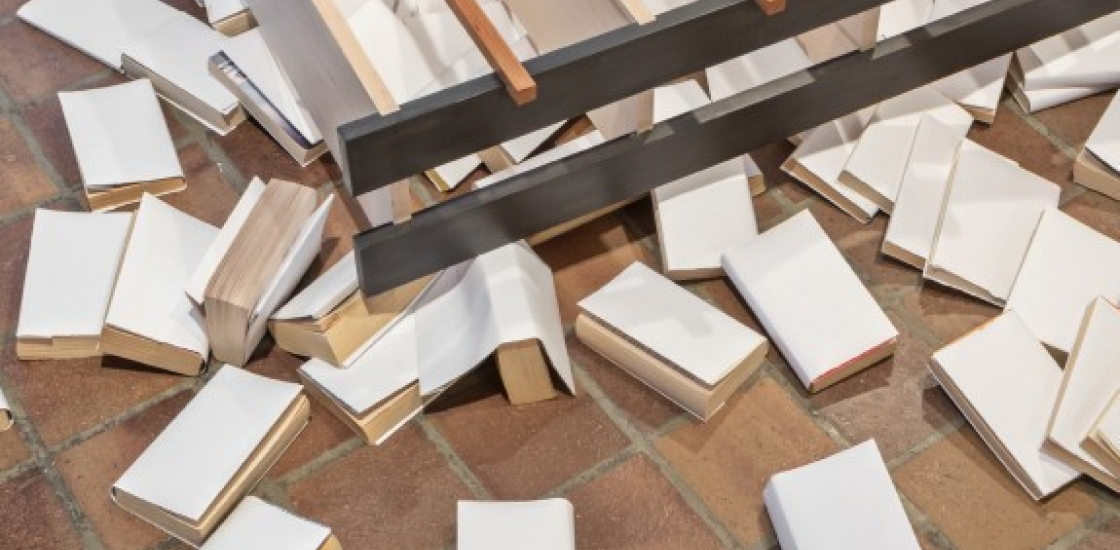 books with white covers scattered on the floor around a low laying structure
