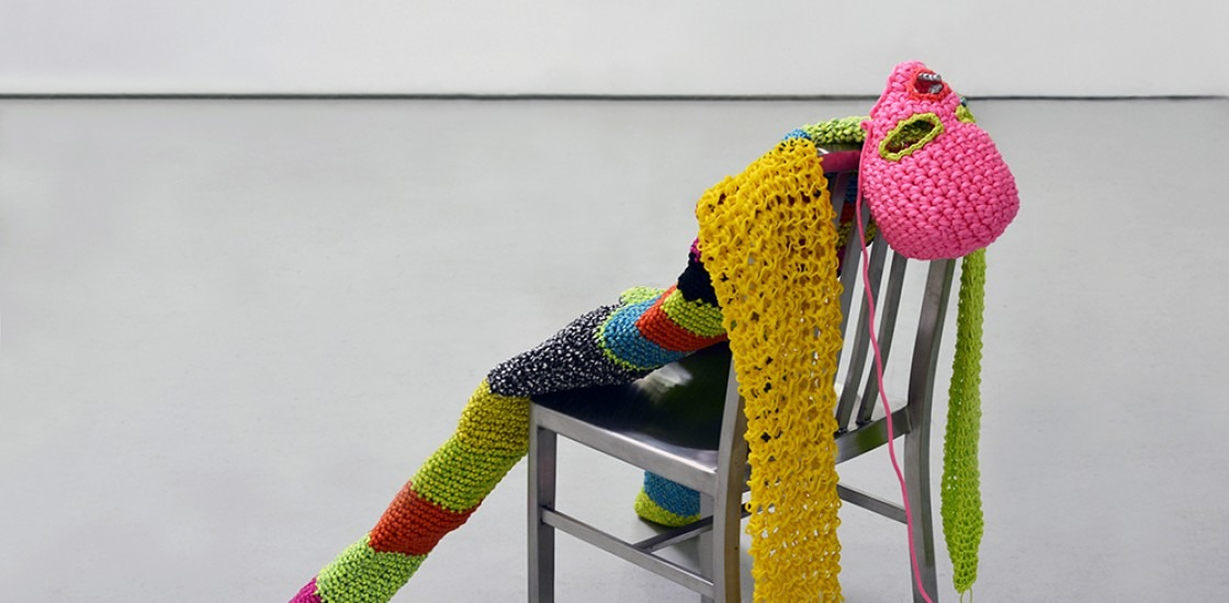 Image of brightly coloured crocheted person lying against chair